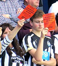 """Newcastle fans show """"Mike Ashley Out"""" cards away to QPR, May 2015"""