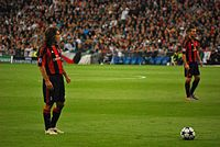 Pirlo (left), with Milan, preparing to take a free kick against Real Madrid in the 2010–11 UEFA Champions League