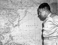 Leslie Groves, Manhattan Project director, with a map of Japan