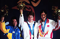 Gold medallist Nancy Johnson (centre) of the U.S., raises her hands with silver medallist Cho-Hyun Kang (left), of South Korea, and bronze winner Gao Jing (right), of China, during the first medal ceremony of the 2000 Olympic Games.