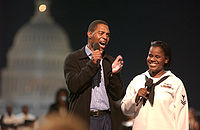 Marcus Allen with Yeoman 2nd Class Katherine Ward introduce Aretha Franklin during a concert in tribute to U.S. military members on the National Mall, September 4, 2003