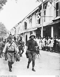 Japanese troops march through the streets of Labuan on 14 January 1942.