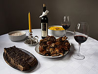 Typical Christmas table in Serbia with roasted pork, Russian salad and wine
