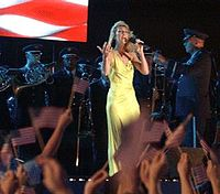 "Dion performing ""God Bless America"" with members of the Band of the US Air Force Reserve, 2002"