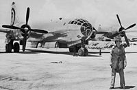 Wearing a helmet and flak jacket and standing in front of The Great Artiste, Tinian 1945