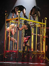 """Spears performing """"Piece of Me"""" inside a cage while her dancers chase her."""