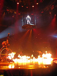 """Spears being lifted into the air in a platform, with a ring of fire in the main stage, during a performance of """"I'm a Slave 4 U""""."""