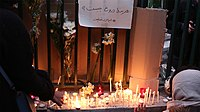 """A gathering at Amirkabir University of Technology. Above flowers and lit candles a notice reads """"What is the cost of lying?"""""""