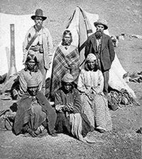 L to R, standing: US Indian agent, Winema (Tobey) Riddle, a Modoc; and her husband Frank Riddle, with four Modoc women sitting in the front two rows. Photographed by Eadweard Muybridge, 1873.