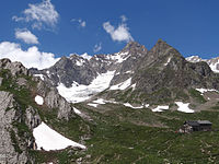alt=Mountain with glacier and mountain hut below Aiguille des Glaciers summit ({{convert 3816 m ft}}) bordering Italy and France, the watershed between the rivers Arve, Isère and Dora Baltea, and the site of a fatal plane crash in 1946