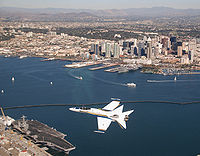 F/A-18 Hornet flying over San Diego and the USS John C. Stennis