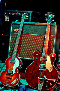 """A Höfner """"violin"""" bass guitar and Gretsch Country Gentleman guitar, models played by McCartney and Harrison, respectively; the Vox AC30 amplifier behind them is the model the Beatles used during performances in the early 1960s."""