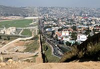 To the left lies San Diego, California and on the right is Tijuana, Baja California. The building in the foreground on the San Diego side is a sewage treatment plant built to clean the Tijuana River.