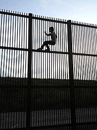 Climbing the Mexico–United States barrier fence in Brownsville, Texas