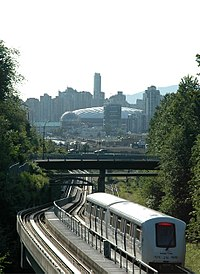 Vancouver's SkyTrain in the Grandview Cut, with downtown Vancouver in the background. The white dome-like structure is the old roof of BC Place Stadium.