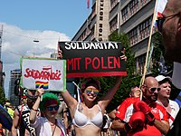 Marcher in 2019 Christopher Street Day 2019 march holding up Solidarity sign with Poland, following Białystok attack