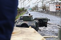 Department of Defense vehicles traveling through a major highway in San Juan flooded with the Hurricane Maria rainfall