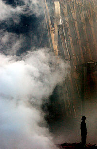 A fireman can be seen in silhouette at the base of the rubble.