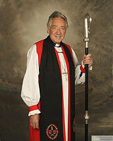 An Anglican bishop with a crosier, wearing a rochet under a red chimere and cuffs, a black tippet, and a pectoral cross