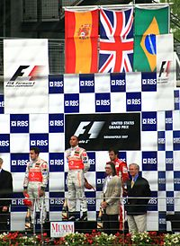 Hamilton on the top podium position after winning the 2007 United States Grand Prix. He is flanked by teammate Fernando Alonso (left) and Felipe Massa (right).