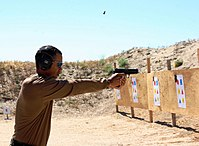 Woods fires a handgun at a shooting range outside San Diego.