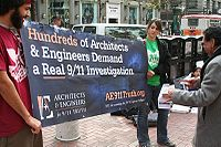 Two people holding a banner of Architects & Engineers for 9/11 Truth