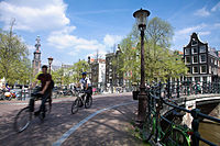 Police bicyclist crossing a bridge over the Prinsengracht