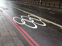 Olympic rings marked on a street, indicating that the lane is reserved for the use of Olympic athletes and staff