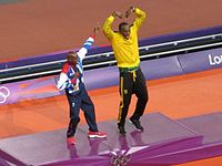 """Mo Farah (left) with Usain Bolt (right), demonstrating one another's famous gestures (the """"Lightning Bolt"""" and """"Mobot"""")"""
