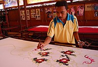 A craftsman making batik. Malaysian batik is usually patterned with floral motifs with light colouring.