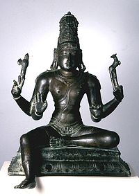 A seated Shiva holds an axe and deer in his hands.