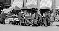 """Carts selling frankfurters, the predecessor to hotdogs, in New York circa 1906. The price is listed as """"3 cents each or 2 for 5 cents""""."""