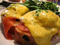 Eggs Benedict, an American breakfast dish made with poached eggs and hollandaise sauce, served in this variation with smoked salmon
