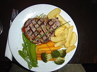 A sirloin steak dinner served with sauteed onion, fries, broccoli florets, cut carrots, whole snow peas, and garnished with whole chives