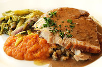 A modern dish consisting of traditional roasted turkey, sweet potatoes, and grilled vegetables prepared with modern fusion ingredients
