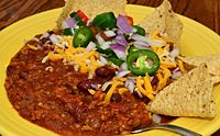 Chili con carne, a typical Tex-Mex dish with garnishes and tortilla chips