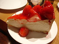 New York–style cheesecake with strawberries. Other variations include blueberry or raspberry sauce.