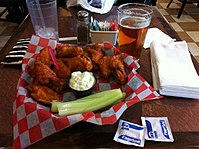 Buffalo wings with blue cheese dressing, served with lager beer.