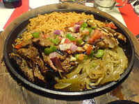 Mixed beef and chicken fajita ingredients, served on a hot iron skillet