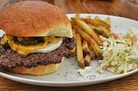 A cheeseburger served with fries and coleslaw
