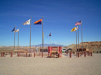 Flags surrounding the Four Corners Monument. In clockwise order starting from the frontmost flag, the state flag of Arizona, Flag of the Navajo Nation (twice), Utah, Ute Mountain Ute Tribe Reservation, Colorado, New Mexico, Navajo Nation (third instance), and the flag of the United States.