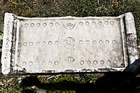 Stone game board from Aphrodisias: boards could also be made of wood, with deluxe versions in costly materials such as ivory; game pieces or counters were bone, glass, or polished stone, and might be coloured or have markings or images