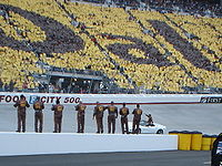 Dale Jarrett on a parade lap before his final points race as fans and crew applaud him