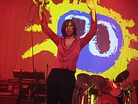 Primal Scream performing live with the cover of their album Screamadelica in the back