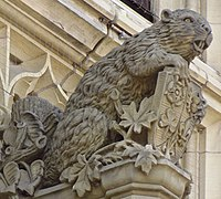 The mother beaver on the Canadian parliament's Peace Tower. The five flowers on the shield each represent an ethnicity—Tudor rose: English; Fleur de lis: French; thistle: Scottish; shamrock: Irish; and leek: Welsh.