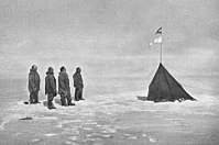 Roald Amundsen and his crew looking at the Norwegian flag at the South Pole, 1911