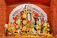 alt=Picture of a many-armed goddess with long black hair and a crown|A murti, or representation, of the goddess Durga shown during the Durga Puja festival
