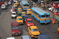 A road in Kolkata showing buses, taxis, auto rickshaws, cars, and other modes of road transport