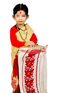 Girl in traditional Mekhela chador dress with aDhol wrapped with Gamosa