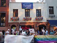 The Stonewall Inn in the gay village of Greenwich Village, Manhattan, site of the June 1969 Stonewall riots, the cradle of the modern LGBT rights movement and an icon of LGBT culture, is adorned with rainbow pride flags.